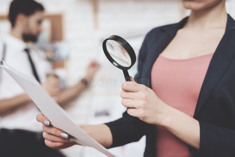 Agencia detective privada La mujer está presentando con el papel y la lupa, hombre está mirando el mapa de las pistas foto de archivo libre de regalías