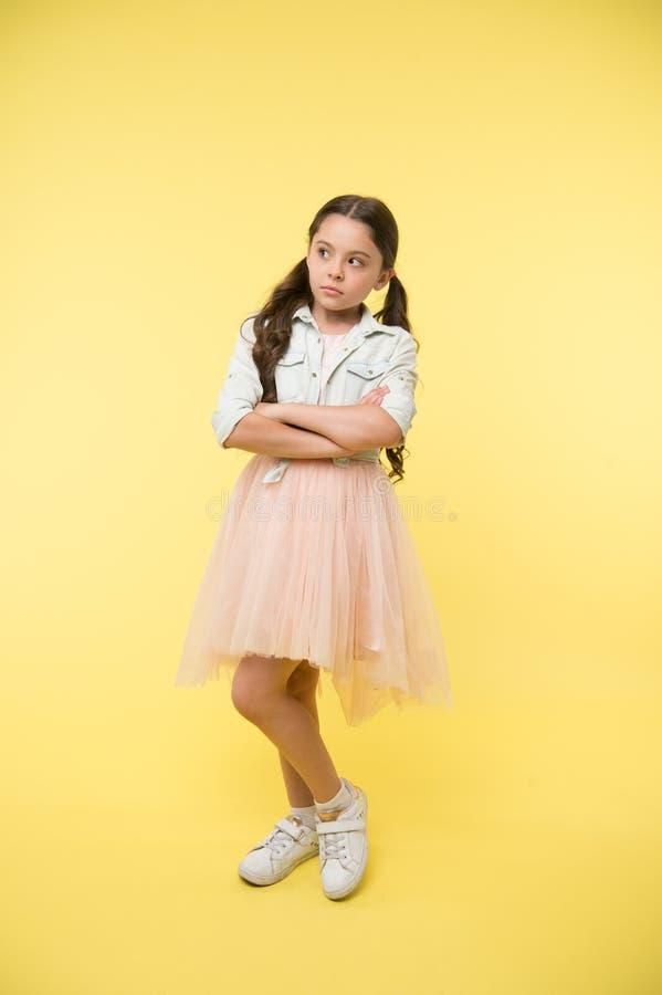 Agencia modelo de moda para los niños El niño mantiene los brazos cruzados en fondo amarillo Actitud de la niña con mirada seria  fotos de archivo libres de regalías