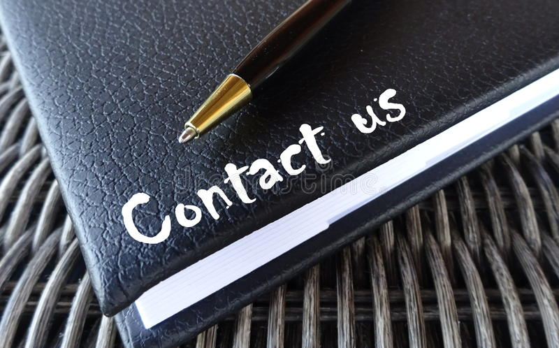 Contact us concept with agenda and pen. Close up of blue leather agenda for planning appointment and meeting. A black pen on top. Contact us in white letters on royalty free stock images