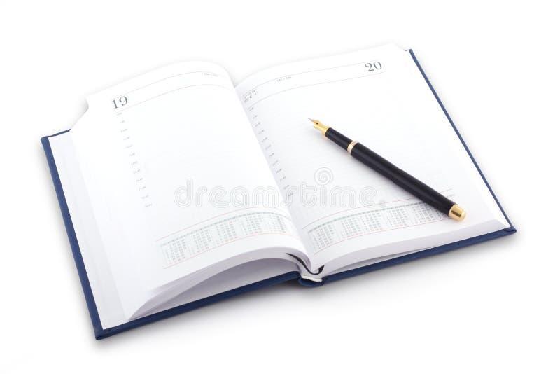 Agenda e pena no fundo branco imagem de stock royalty free