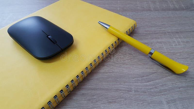 Agenda met pen en muis op houten bureau stock fotografie