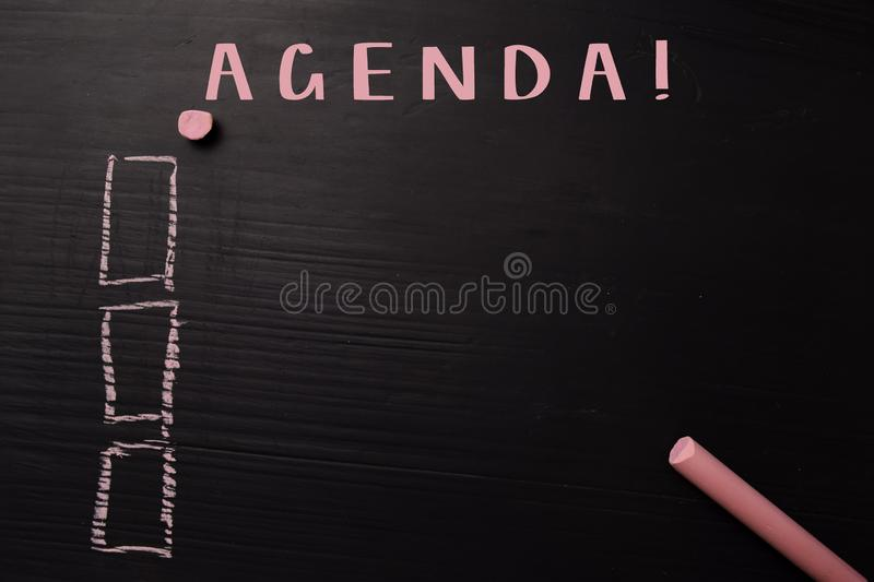Agenda! written with color chalk. Supported by an additional services. Blackboard concept royalty free stock photography