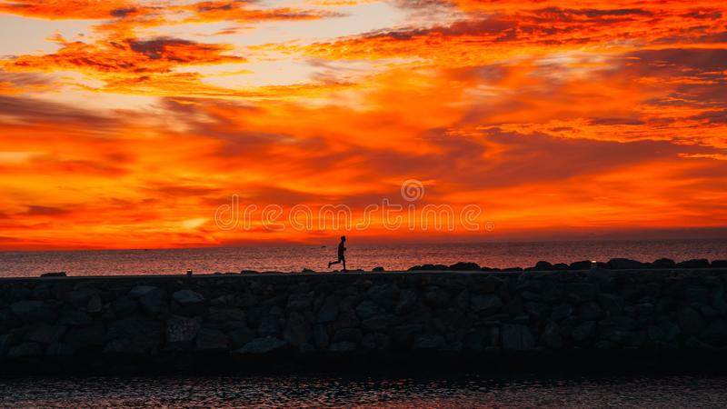 Agent bij zonsopgang die naast het overzees lopen royalty-vrije stock afbeelding