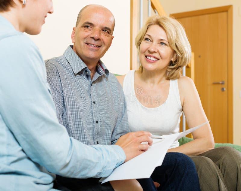 Agent de écoute de couples mûrs avec le papier image stock