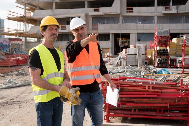 Agent de maîtrise au travail avec un travailleur de la construction image stock