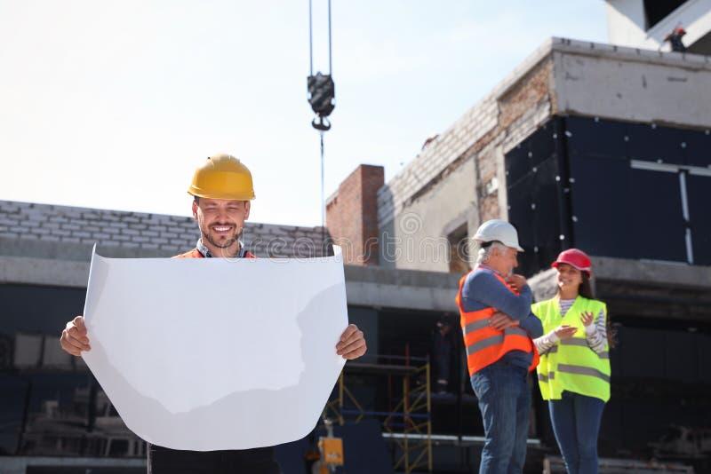 Agent de maîtrise avec la rédaction et ingénieurs professionnels dans le dispositif de protection au chantier de construction images stock