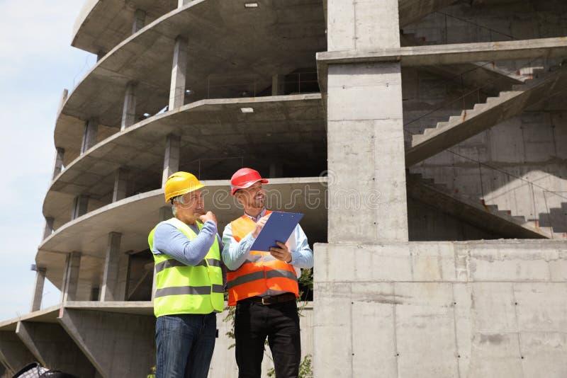 Agent de maîtrise avec le presse-papiers et l'ingénieur professionnel dans le dispositif de protection au chantier de constructio image libre de droits