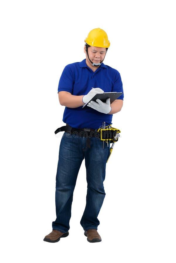 Agent de maîtrise de construction dans la chemise bleue avec les gants protecteurs, casque avec le presse-papiers de participatio photos libres de droits