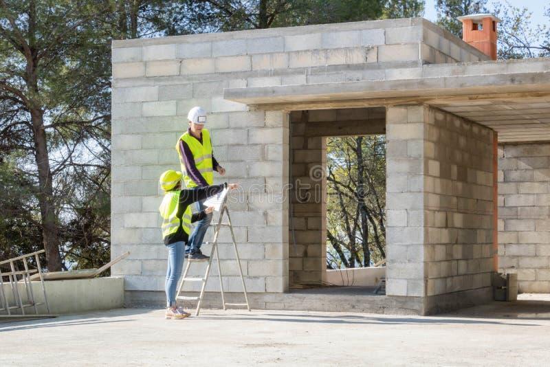 Agent de maîtrise et son jeune apprenti lors d'une visite du site de construction, maison en construction photo stock