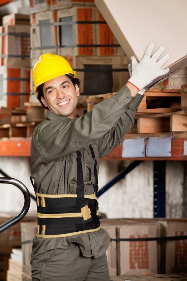 Agent de maîtrise Lifting Cardboard Box à l'entrepôt photo stock