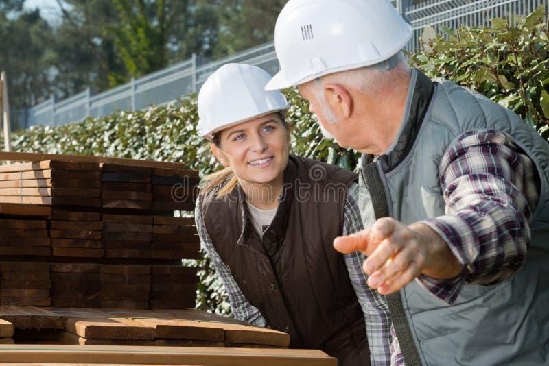 Agent de maîtrise parlant au main-d'œuvre féminine par le bois planked courant photographie stock libre de droits