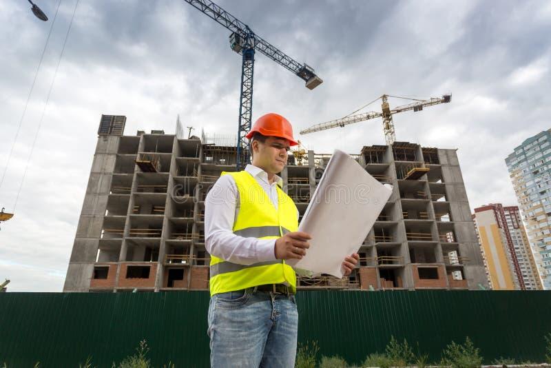 Agent de maîtrise regardant sur des modèles le chantier photographie stock libre de droits