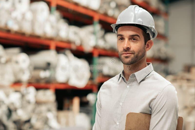 Agent de maîtrise utilisant un casque antichoc sur son plancher d'entrepôt images stock