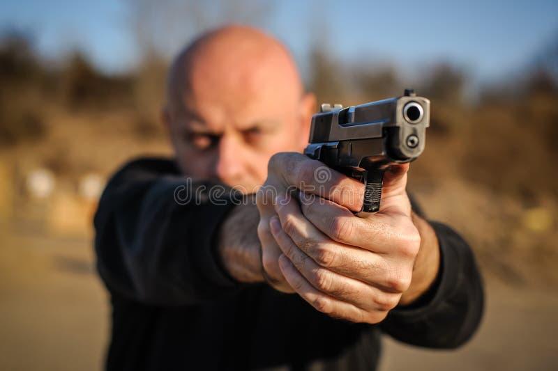 Agent de police et garde du corps dirigeant le pistolet pour se protéger contre l'attaquant photos stock
