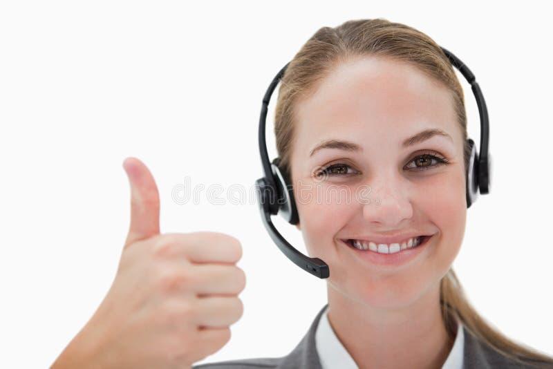 Agent de sourire de centre d'attention téléphonique renonçant au pouce images stock