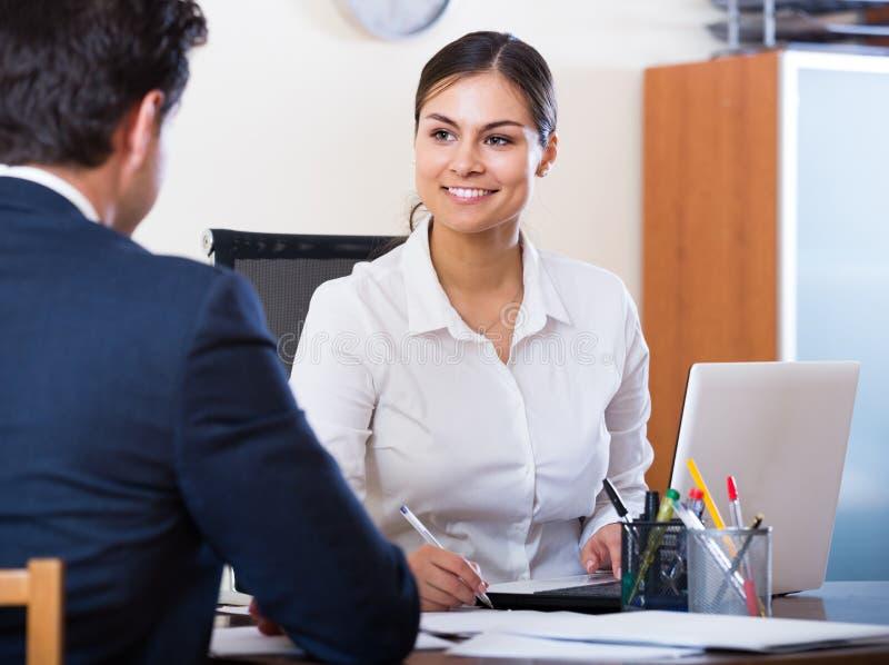 Agent die aan klant luisteren en in agentschap glimlachen stock foto
