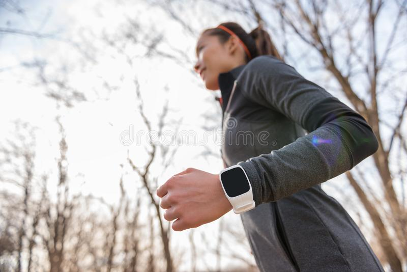 Agent die smartwatch op polsclose-up dragen Het jonge geschiktheidsvrouw lopende uitwerken cardio in de herfst of de winteraard i royalty-vrije stock fotografie