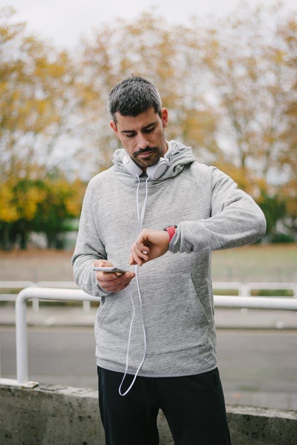 Agent die sportief slim horloge en smartphone voor opleiding gebruiken royalty-vrije stock foto