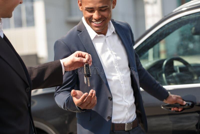 Agent donnant des clés à la position de porte d'ouverture de jeune homme près de la voiture heureuse image libre de droits