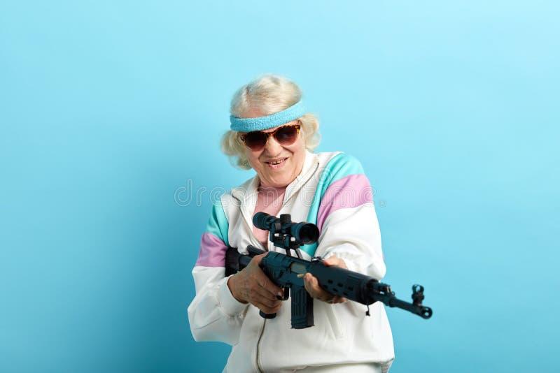 Agent du FBI de regard gentil de grand-m?re visant avec un fusil, pr?t ? tirer, affiche photographie stock libre de droits