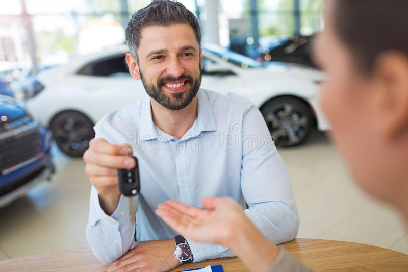 Agent Giving Car Key To Woman. Car dealer with a female buyer stock photos
