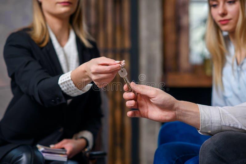 Agent immobilier élégant avec l'argent sur la main donnant la clé de l'appartement, maison aux jeunes couples images libres de droits