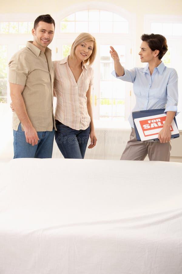 Agent immobilier affichant autour des couples image libre de droits