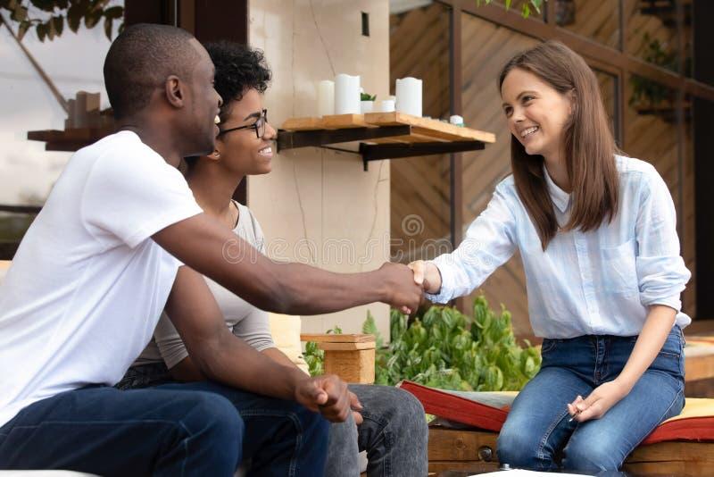 Agent immobilier africain heureux d'assureur de poignée de main de clients de couples faisant l'affaire photos libres de droits