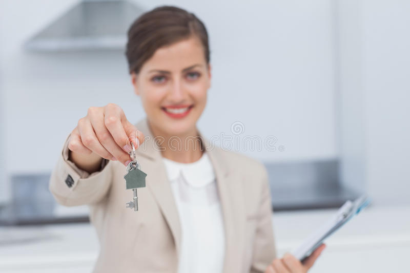 Agent immobilier assez vrai donnant la clé de maison photographie stock