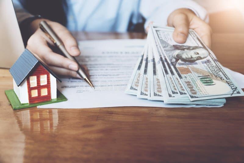 Agent immobilier avec le modèle de maison tenant l'argent et dirigeant le stylo photos libres de droits