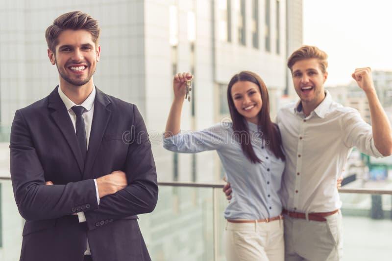 Agent immobilier bel et couples heureux image stock