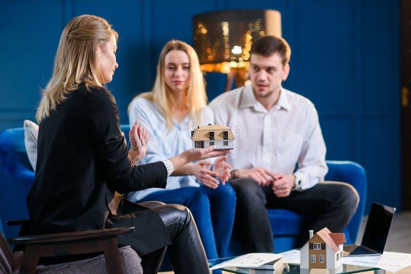Agent immobilier caucasien femelle, dessinateur d'intérieurs, décorateur sur la réunion avec des couples des clients image libre de droits