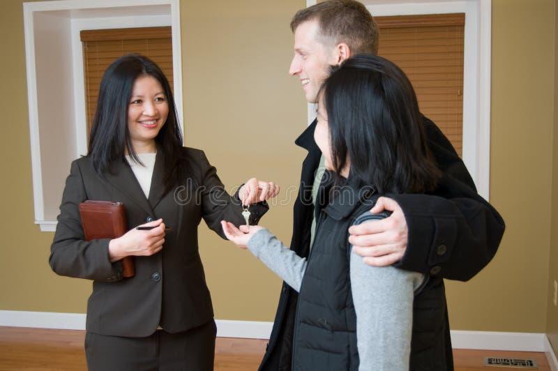 Agent immobilier donnant la clé aux couples images libres de droits