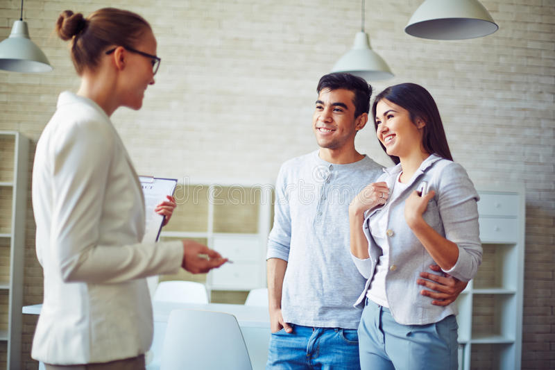 Agent immobilier et couples images stock