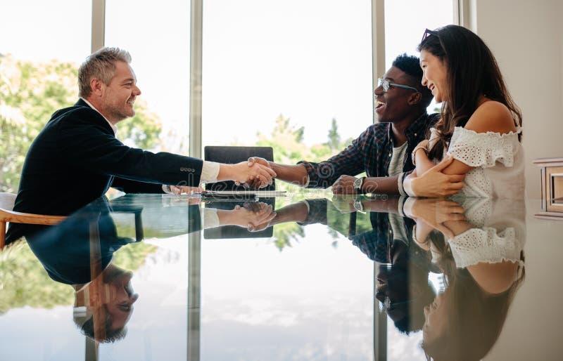 Agent immobilier félicitant des couples après une affaire de propriété image stock