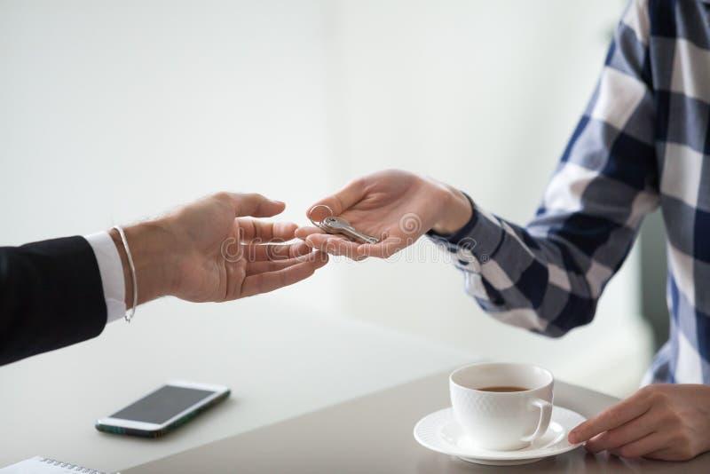 Agent immobilier femelle de propriétaire remettant des clés au client ou au locataire masculin image stock