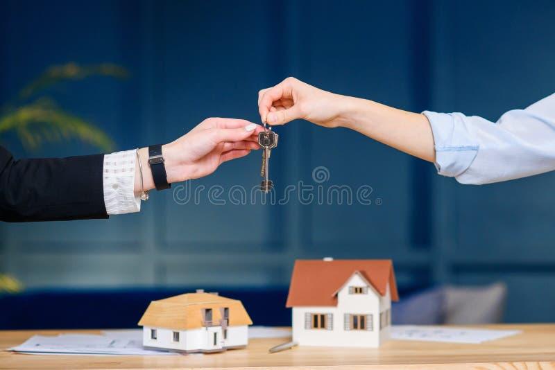 Agent immobilier femelle donnant la cl? du nouvel appartement, maison aux clients f?minins images stock