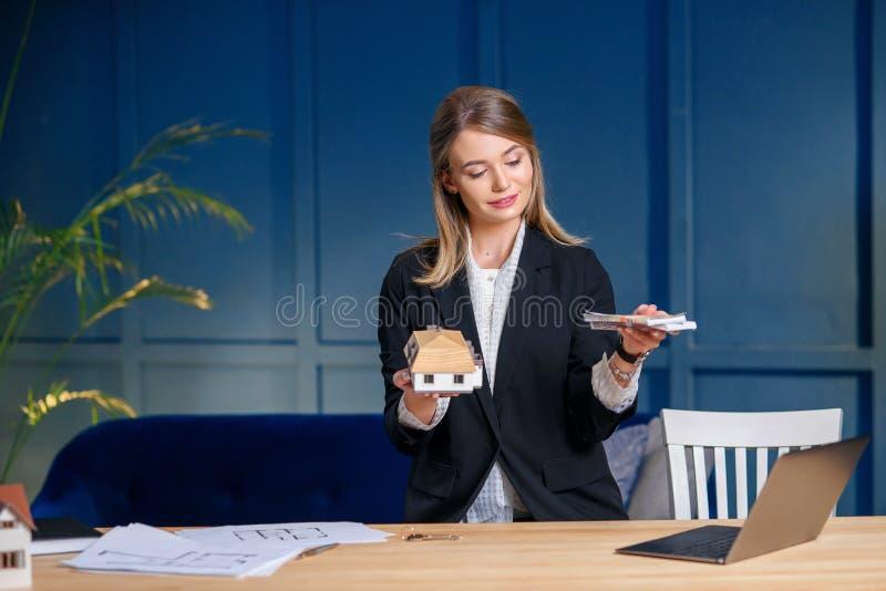 Agent immobilier femelle mignon avec l'argent et le maket 3d de la maison dans des mains sur le fond bleu de mur photographie stock libre de droits