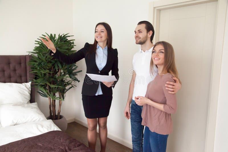 Agent immobilier femelle montrant l'appartement de luxe aux jeunes couples, vraie es image stock
