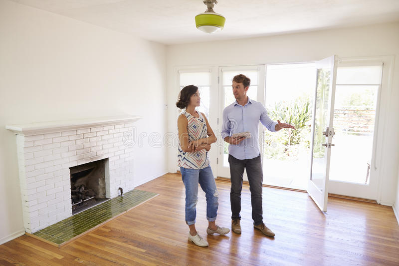 Agent immobilier masculin montrant le client féminin autour de la Chambre photo stock