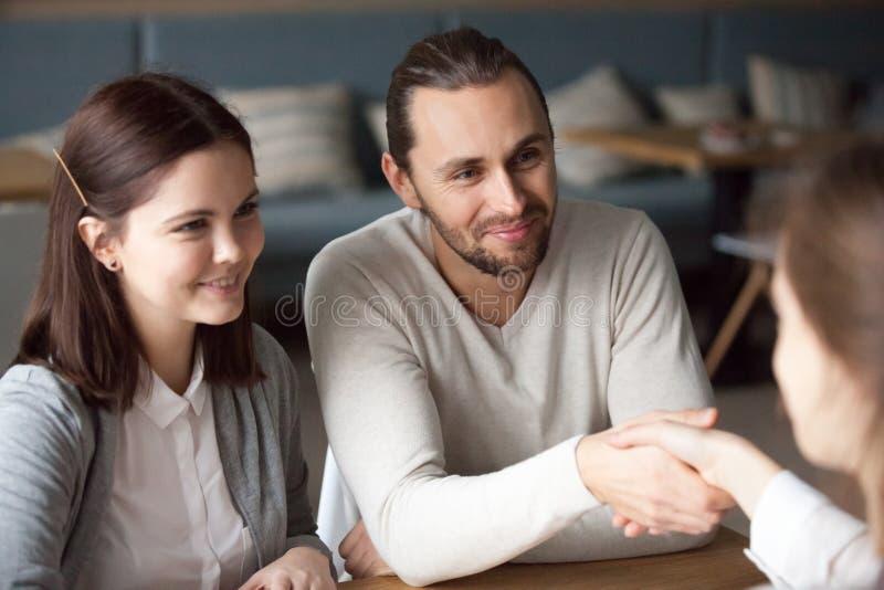 Agent immobilier millénaire heureux de poignée de main de couples pendant se réunir photo libre de droits