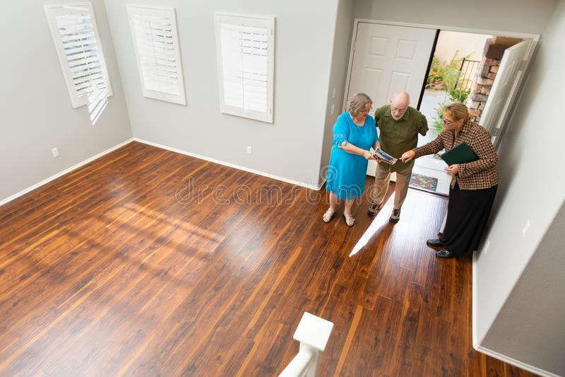 Agent immobilier montrant à couples adultes supérieurs une nouvelle maison photo libre de droits
