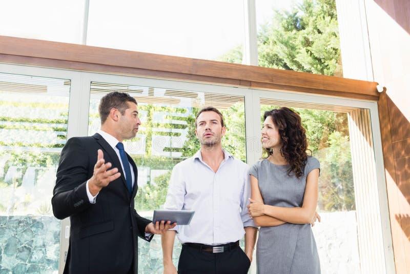 Agent immobilier montrant à couples la nouvelle maison image stock