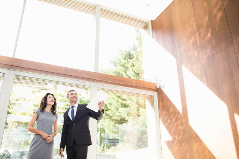 Agent immobilier montrant à jeune femme la nouvelle maison photo libre de droits