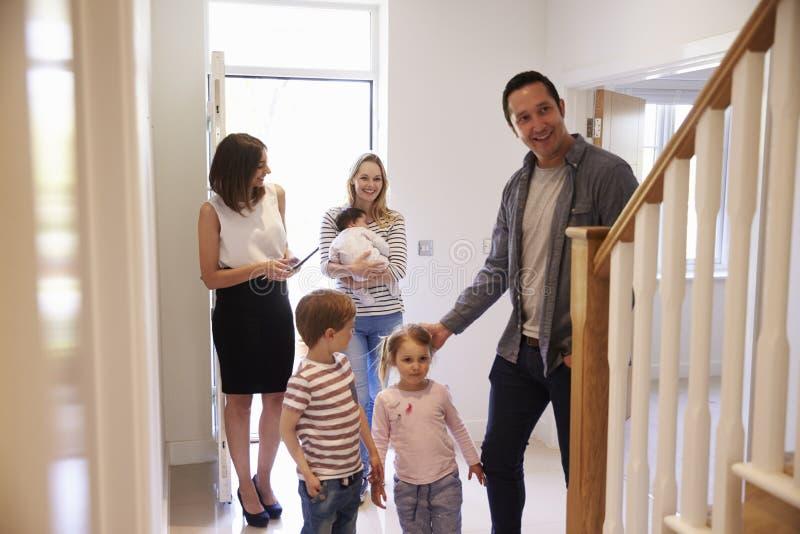 Agent immobilier montrant la jeune famille autour de la propriété à vendre image stock