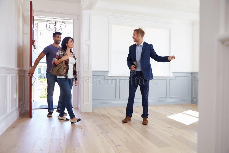 Agent immobilier montrant les couples hispaniques autour de la nouvelle maison images libres de droits