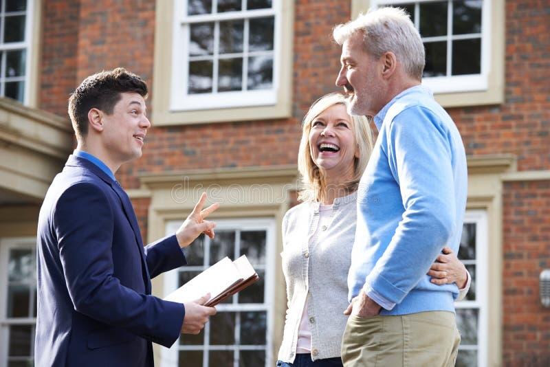 Agent immobilier montrant les couples mûrs autour de la Chambre à vendre image stock