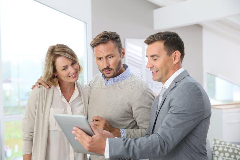 Agent immobilier présentant la nouvelle maison aux clients photo libre de droits