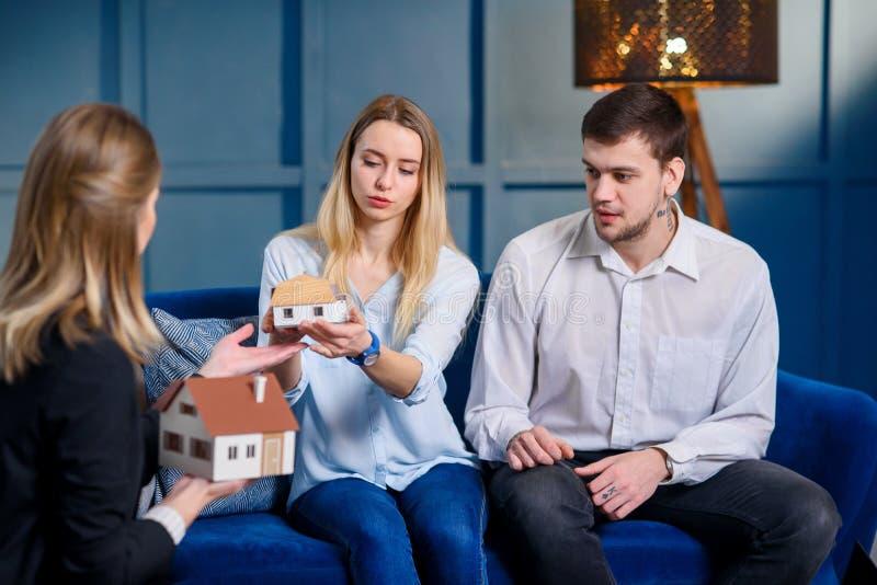 Agent immobilier professionnel, dessinateur d'intérieurs, décorateur discutant la conception avec de jeunes couples élégants photo stock
