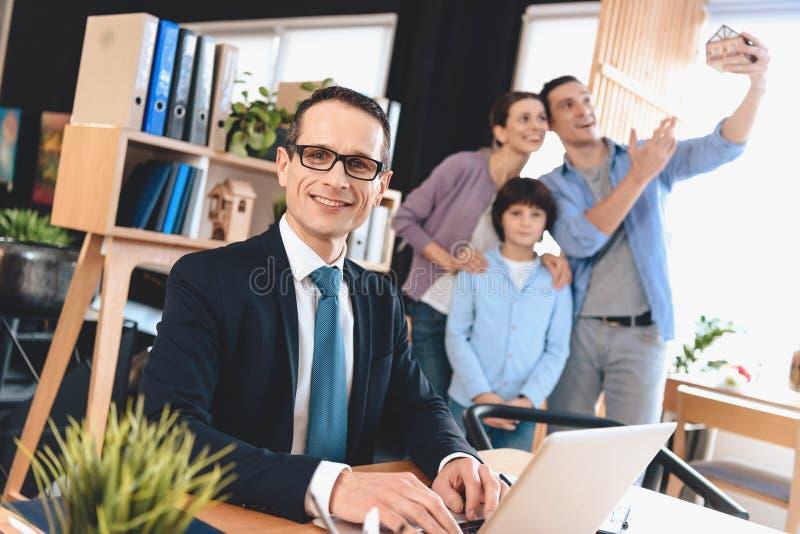 Agent immobilier se reposant au bureau dans le bureau L'agent immobilier travaille sur l'ordinateur portable avec la famille à l' photographie stock libre de droits